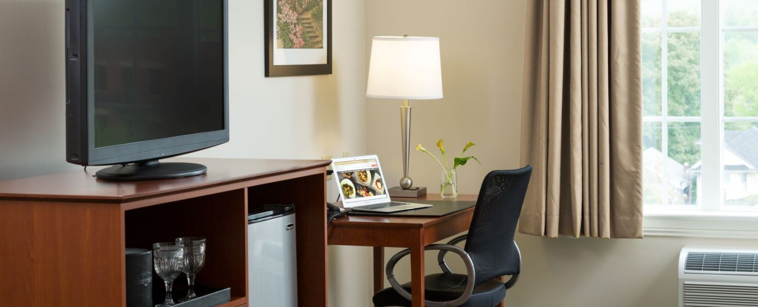 Guest Room with TV Refrigerator and desk with chair