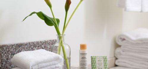 towel, flowers, soap on bathroom counter