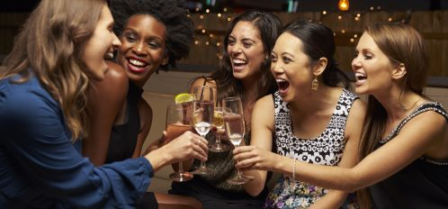 5 women toasting drinks and smiling at a party