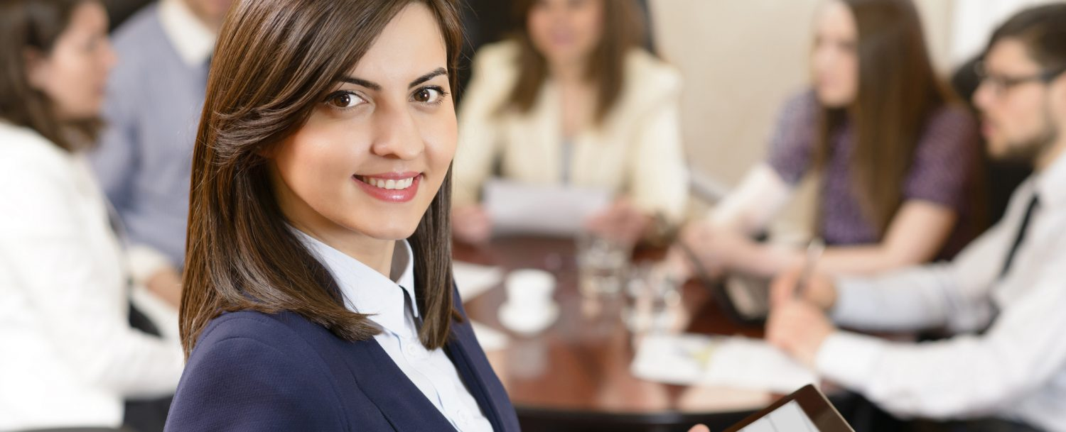 a smiling business woman holding a tablet at a business meeting